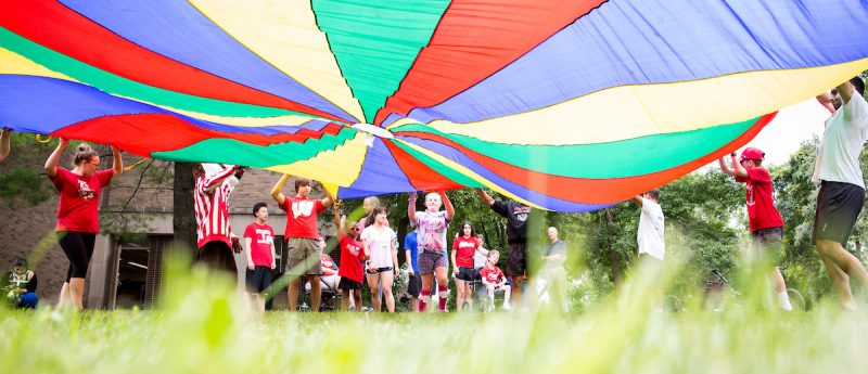 Students playing with a colorful parachute.