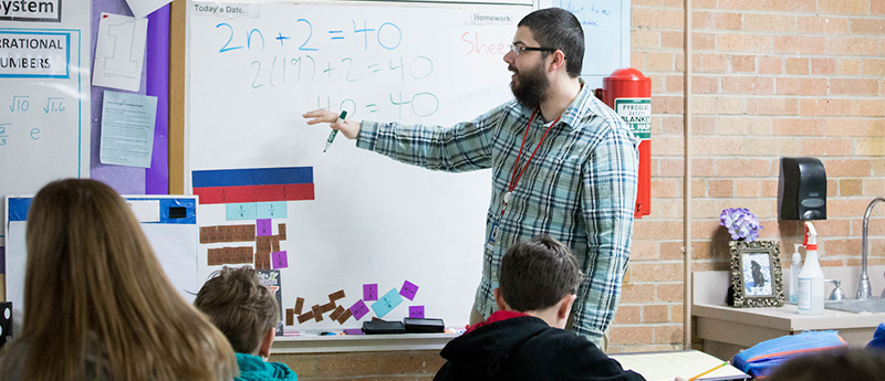 Teacher teaches math class in elementary school classroom