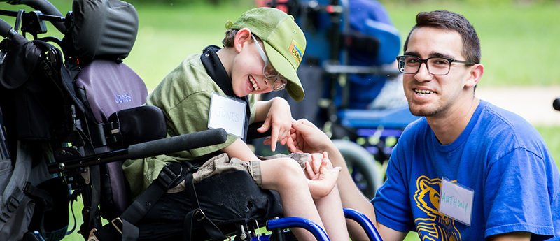 Volunteer interacts with child in wheelchair at event
