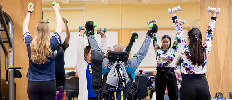 Participants in adaptive fitness class lift weights