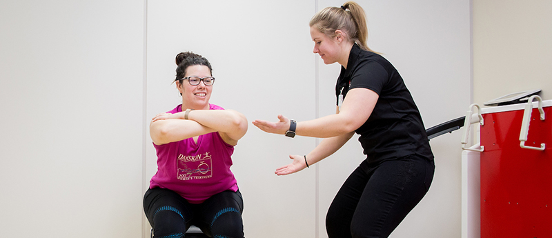 Woman does squat as another instructs her