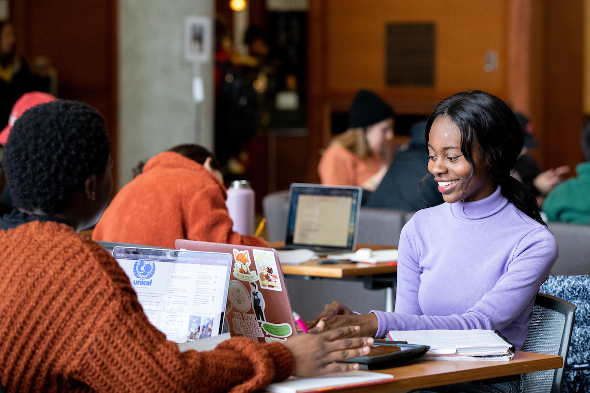 uw madison student sits at study table with another student and laptops