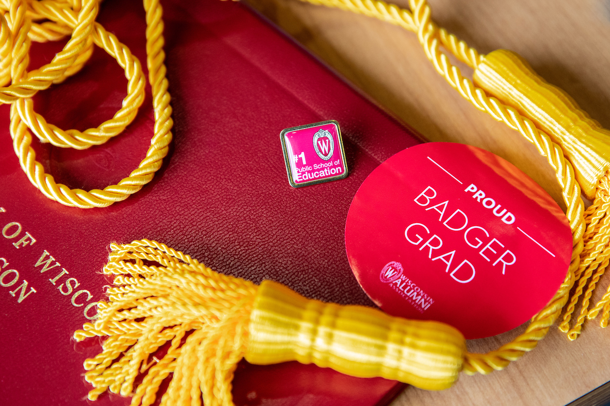 uw-madison diploma beneath tassels, pin, and button saying proud badger grad